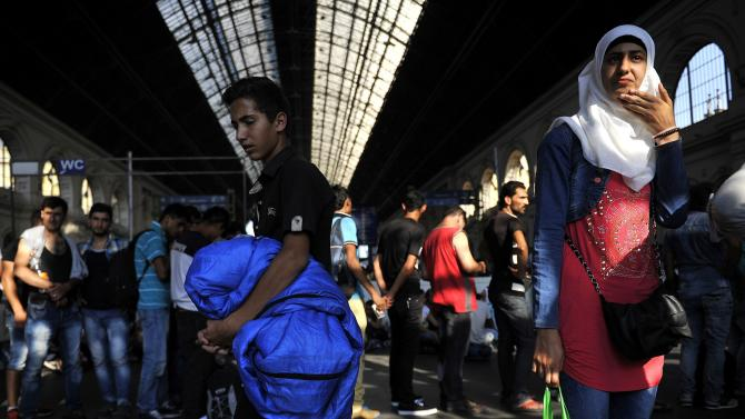 Migrants wait to board the train that will take them towards Munich, Germany at the Keleti Railway Station in Budapest, Hungary, Monday, Aug. 31, 2015. Migrants possessing valid documents and a train ticket are being allowed on international trains at the station.  (Tamas Kovacs/MTI via AP)