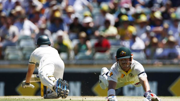 Australia's batsmen Rogers and Warner both dive for the crease as Rogers is run out during the third Ashes cricket test match against England in Perth