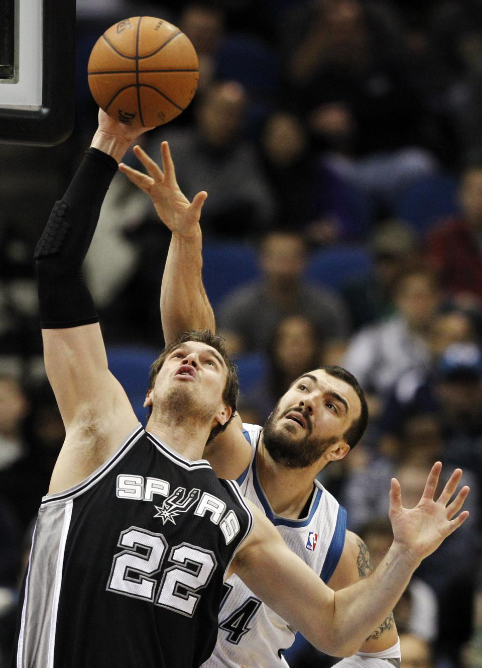 San Antonio Spurs center Tiago Splitter (22), of Brazil, brings down a rebound against Minnesota Timberwolves center Nikola Pekovic (14), of Montenegro, during the first half of an NBA basketball game Wednesday, Feb. 6, 2013, in Minneapolis. (AP Photo/Genevieve Ross)