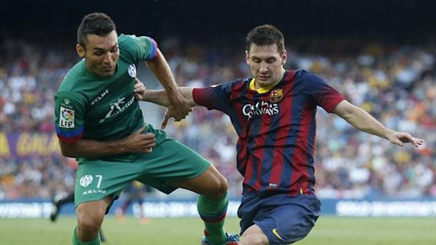Barcelona's Lionel Messi (R) fights for the ball against Levante's David Barral during their Spanish First division soccer league match at Camp Nou stadium in Barcelona, August 18, 2013 (Reuters)
