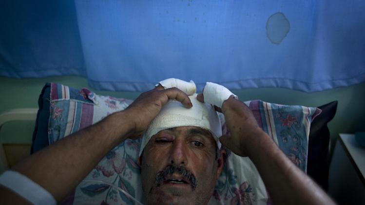 Injured Palestinian shepherd Najeh Abu Ali, 47 receives medical treatment at the main hospital in the West Bank town of Ramallah, Monday, Aug. 19, 2013. The Palestinian shepherd says he was hit in the head and hands by men wielding metal pipes in the vicinity of West Bank Jewish settlers' outposts. (AP Photo/Nasser Nasser)