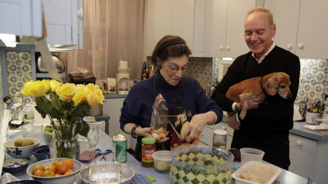 """Karen Nelson, and her house guest Gregory Downer, holding his dashund Ziggy, prepare dinner in her upper west side apartment, in New York, Thursday evening, Nov. 1, 2012. Like herself, her neighbors have taken in dozens of """"refugees,"""" people who have fled their cold, dark homes in search of a roof, food, a hot shower and juice for their cell phones, iPads and laptops. (AP Photo/Richard Drew)"""