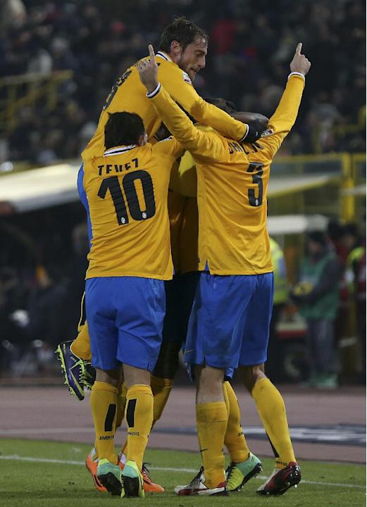 Juventus' Giorgio Chiellini, right, celebrates with teammates Carlos Tevez and Claudio Marchisio, top, after scoring during the Serie A soccer match between Bologna and Juventus at the Dall' A
