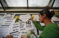 A girl puts flowers on the billboard of a bus stop during a protest march in New Delhi December 29, 2012. A woman whose gang rape sparked protests and a national debate about violence against women in India died of her injuries on Saturday, prompting a security lockdown in New Delhi and an acknowledgement from India's prime minister that social change is needed. REUTERS/Danish Siddiqui