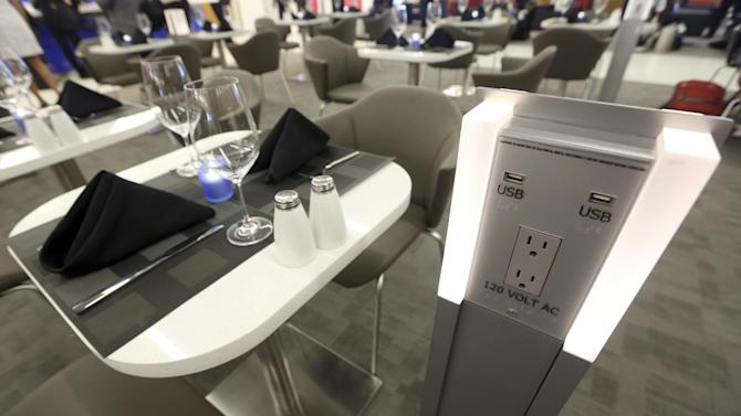 A battery recharge station is positioned next to a a table set up for dining in the Delta airlines Sky club  in terminal 4 at JFK airport, Friday, May 24, 2013 in New York. Delta opened its new $1.4 billion terminal, strengthening its hand in the battle for the lucrative New York travel market. The expanded concourse offers sweeping views of the airport, upscale food and shopping options and increased seating. It replaces a decrepit terminal built by Pan Am in 1960 that was an embarrassing way to welcome millions of visitors to the United States.  (AP Photo/Mary Altaffer)
