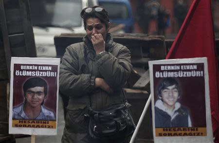 "A woman mourns next to posters with Berkin Elvan's illustrations and slogans reading ""Berkin is immortal"" near Okmeydani Cemevi in Istanbul"