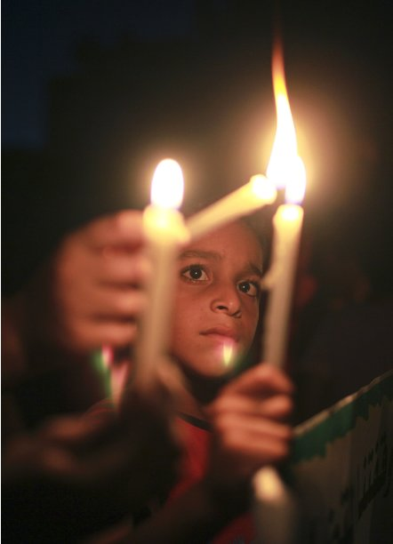 Palestinian boy lights a candle during a protest in the northern Gaza Strip