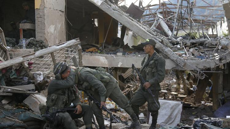 Police officers react amid the ruins of a police station that was destroyed in a bomb attack in Inza