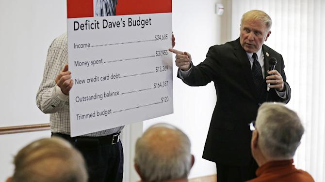 In this photo taken March 25, 2013, Rep. Steve Chabot, R-Ohio, uses a chart to talk about the U.S. budget deficit during a town hall meeting with constituents in Montgomery, Ohio. Here in the Cincinnati suburbs, where people tend to be polite, one finds seeds of the bitter partisanship that gnaws at Washington, 500 miles away. If any Republican House members might be open to compromise with President Barack Obama and Democratic lawmakers, Chabot would seem near the top. Yet he toes an unyielding conservative line on virtually every big issue. (AP Photo/Al Behrman)