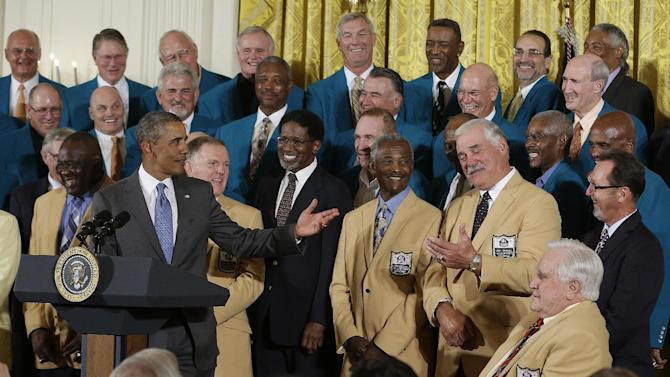 President Barack Obama gestures toward fullback Larry Csonka, during a ceremony in the East Room of the White House in Washington, Tuesday, Aug. 20, 2013, where the president honored the Super Bowl VII football Champion Miami Dolphins. From left are, guard Larry Little, the president, quarterback Bob Griese, wide receiver Paul Warfield, Csonka, and coach Don Shula. (AP Photo/Pablo Martinez Monsivais)