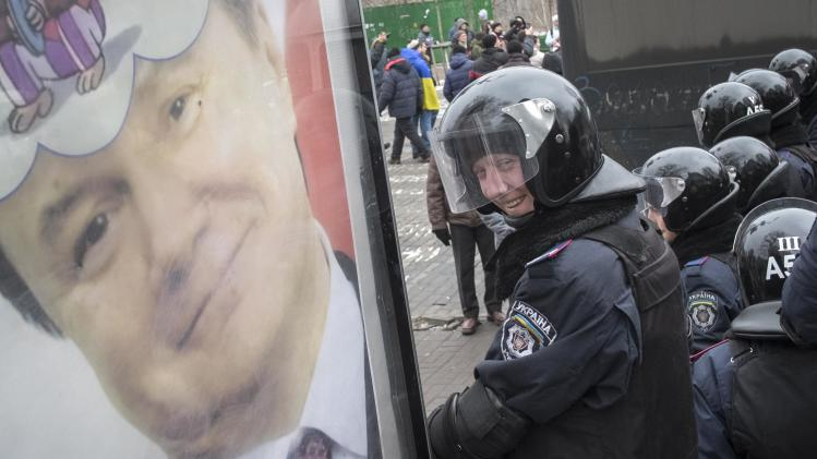 A portrait of Ukrainian President Yanukovich is seen near Interior Ministry personnel as they block pro-EU demonstrators near the Ukrainian Ministry of Internal Affairs in Kiev