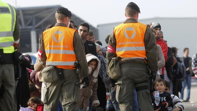 Migrants are guarded by soldiers as they wait for buses in Nickelsdorf