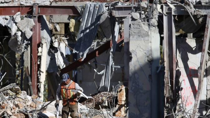 A crew member works to clear debris the day after a deadly gas truck explosion ripped through a maternity hospital in Mexico City