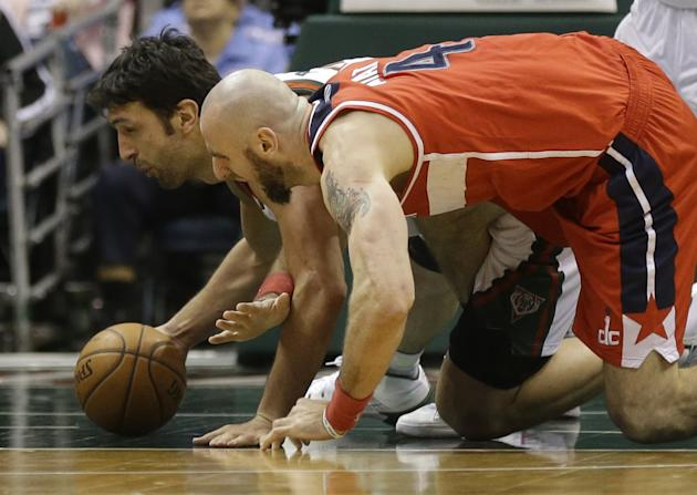 Milwaukee Bucks' ZaZa Pachulia, left, and Washington Wizards' Marcin Gortat go to the floor for a loose ball during the second half of an NBA basketball game on Saturday, March 8, 2014, in Mil