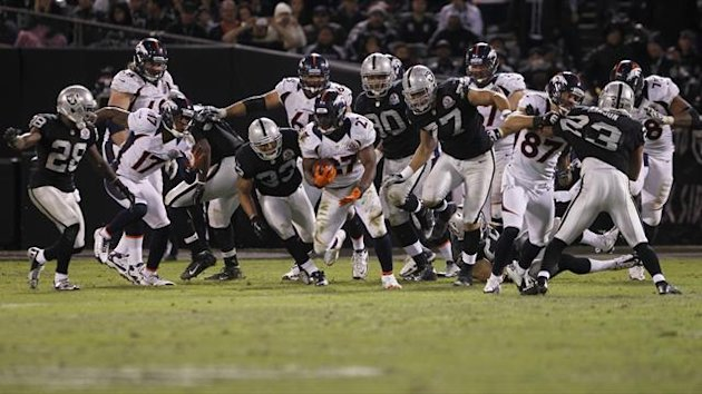 Denver Broncos running back Knowshon Moreno (C) runs against the Oakland Raiders defence