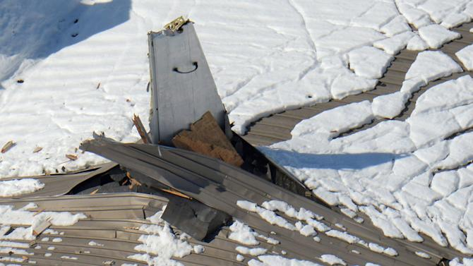 The vertical tail of a plane sticks out of the sagging roof of a hangar after heavy snowfall at Nippi Corp.'s aircraft maintenance and repair division in Yamamo, near Tokyo, Sunday, Feb. 14, 2014. The second heavy snowfall this month has hit eastern Japan, killing more than 10 people and injuring hundreds, while paralyzing traffic and causing power outages. Japan's weather agency said Sunday that the low pressure system was traveling north, dumping more snow to the area after passing the Tokyo region. (AP Photo/Kyodo News) JAPAN OUT, CREDIT MANDATORY