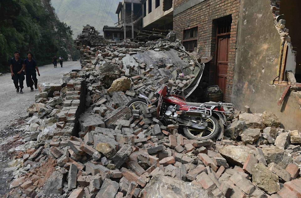 People walk past damaged buildings at a quake-hit Luozehe town in Yiliang county in southwest China's Yunnan province Saturday, Sept. 8, 2012. Rescue workers cleared roads Saturday so they could search for survivors and rush aid to a remote mountainous area of southwestern China after twin earthquakes killed at least 80 people. (AP Photo)