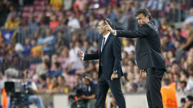 Barcelona's coach Luis Enrique gestures to his players near Apoel FC's coach Giorgos Donis during their Champions League soccer match at Nou Camp stadium in Barcelona