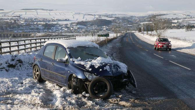 A crashed car stands abandoned on a snow covered verge near Sheffield,