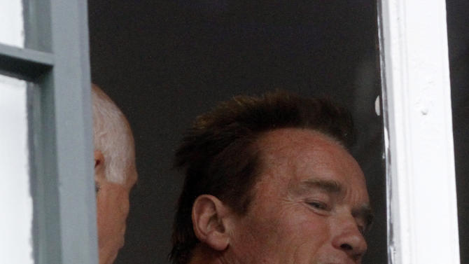 Former Californian governor Arnold Schwarzenegger looks out of a window during an inauguration ceremony of the Arnold Schwarzenegger museum in the house where he was born in Thal near Graz, Austria, on Friday, Oct. 7, 2011. (AP Photo/Ronald Zak)