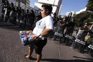 A street vendor walks past a police blockade during a protest by supporters of presidential candidate Castro in Tegucigalpa
