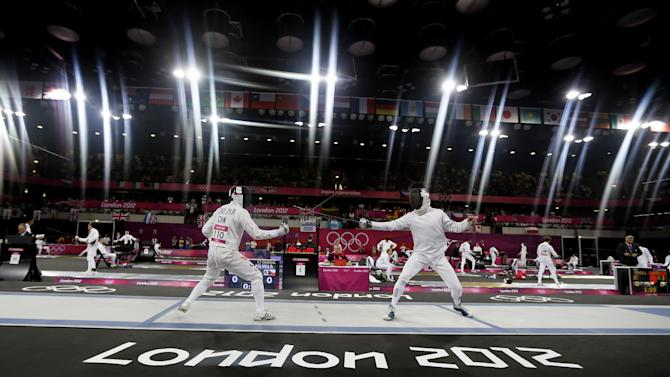 Cao Zhongrong of China, left, and Ondrej Polivka of the Czech Republic compete during the fencing section of the men's modern pentathlon at the 2012 Summer Olympics, Saturday, Aug. 11, 2012, in London. (AP Photo/Kirsty Wigglesworth)