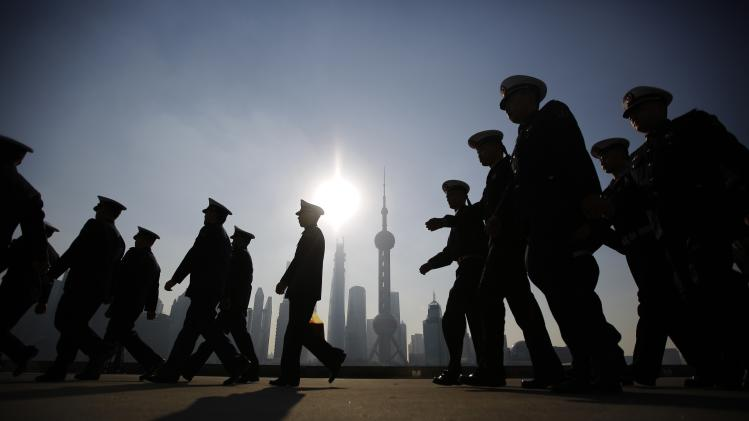 Chinese navy officers prepare for the arrival of the British Royal Navy destroyer HMS Daring to the north side of the bund at Huangpu River in Shanghai