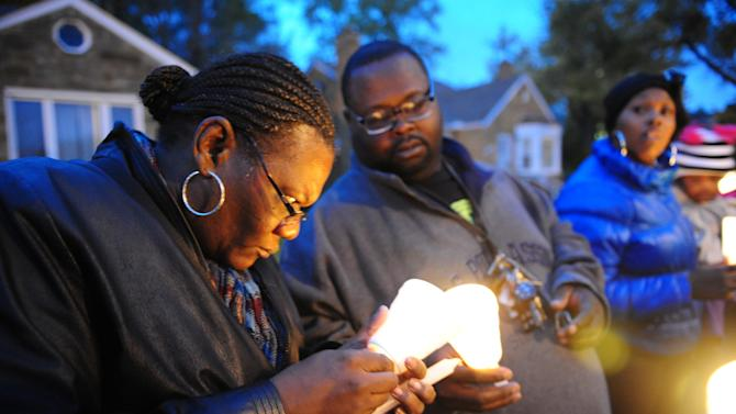 In this Wednesday, Nov. 6, 2013 photo, Charles Hannah lights Theresa Walker's candle, left, at a candlelight vigil for Renisha McBride in the front of the home where she was shot in Dearborn Heights, Mich. No charges have been filed after authorities said McBride, of Detroit, was killed by a shotgun blast to the face early Saturday in Dearborn Heights. According to police, the homeowner told investigators that he thought someone was trying to break into his home and accidentally discharged the gun. (AP Photo/Detroit News, Ricardo Thomas) DETROIT FREE PRESS OUT; HUFFINGTON POST OUT