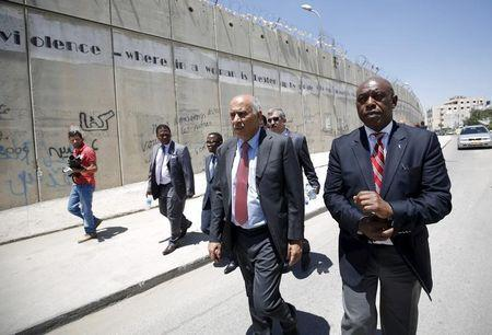 Head of the Palestinian Football Association Rajoub walks with anti-apartheid activist Sexwale past Israel's controversial barrier as they arrive for a news conference in the West Bank town of Al-Ram