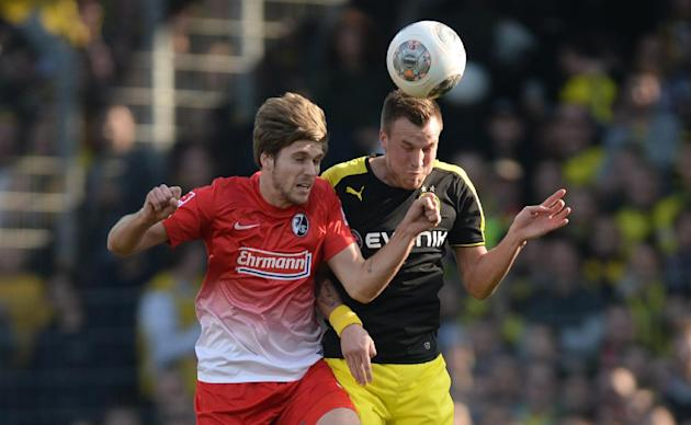 Freiburg's Julian Schuster, left, challenges for the ball with Dortmund's Kevin Grokreutz during the German first division Bundesliga soccer match between SC Freiburg and Borussia Dortmund in