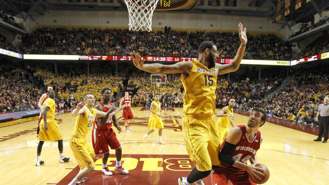 Wisconsin forward Frank Kaminsky (44) goes to the basket under pressure from Minnesota forward Maurice Walker (15) during the first half of an NCAA college basketball game in Minneapolis, Thursday, March 5, 2015. (AP Photo/Ann Heisenfelt)