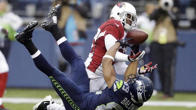 Arizona Cardinals cornerback Jerraud Powers, top, breaks up a pass intended for Seattle Seahawks wide receiver Doug Baldwin in the second half of an NFL football game, Sunday, Dec. 22, 2013, in Seattle. (AP Photo/Elaine Thompson)