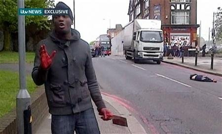 A man with bloodied hands and knives appears in a still image from amateur video that shows the immediate aftermath of an attack in which a man was killed in southeast London