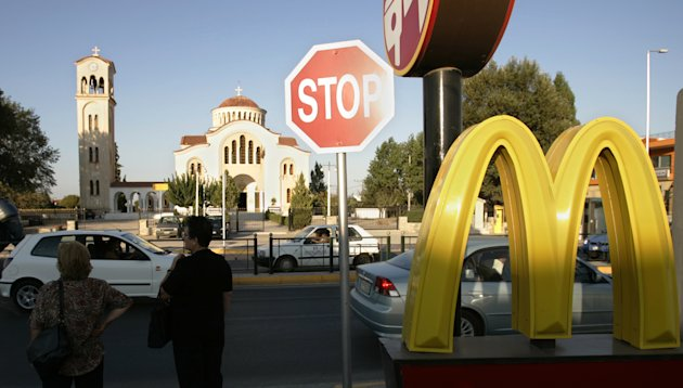 FILE - In this Aug. 19, 2004 file photo, commuters stand near a McDonald&#39;s restaurant in Marathon, Greece. McDonald&#39;s Corp. says a key revenue figure came in flat in July as diners pulled back amid a persistently weak economy. After years of outperforming rivals by emphasizing value and rolling out popular new items, the stall is also a sign that competition is intensifying for the world&#39;s biggest hamburger chain. The figure dipped 0.6 percent in Europe because of weakness in Germany and several Southern European markets. It fell 1.5 percent in the Asia Pacific, Middle East and Africa region, a key growth area for McDonald&#39;s. (AP Photo/Lefteris Pitarakis)