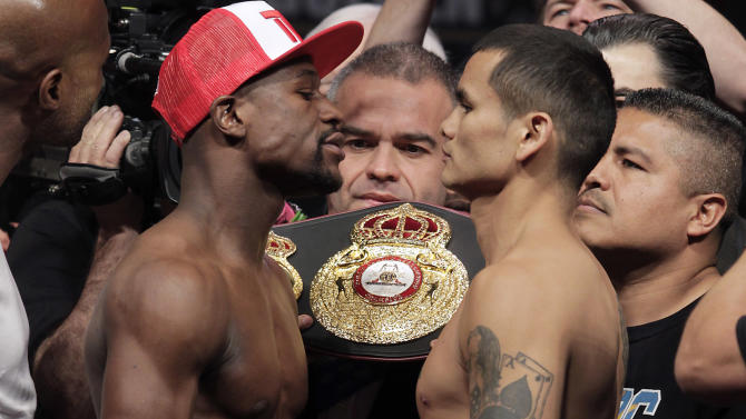 In this May 2, 2014 photo, Floyd Mayweather Jr. (L) of the US poses with Marcos Maidana of Argentina during their weigh-in at the MGM Grand, in Las Vegas on May 2, 2014