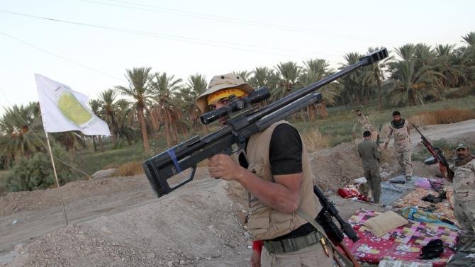 A Shi'ite fighter carries his weapon during a patrol in Jurf al-Sakhar