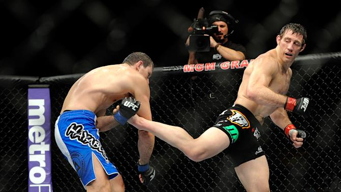 Tim Kennedy connects with a kick on Roger Gracie during their UFC 162 mixed martial arts middleweight bout at the MGM Grand Garden Arena on Saturday, July 6, 2013, in Las Vegas. kennedy won the fight y an unanimous decision after three rounds. (AP Photo/David Becker)