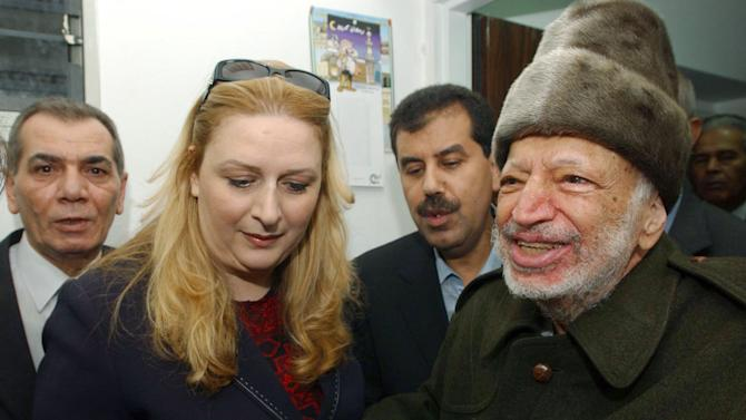 FILE - In this Friday, Oct. 29, 2004 file photo, Palestinian leader Yasser Arafat and his wife Suha hold hands prior to Arafat's departure from his compound in the West Bank town of Ramallah in this file picture released by the Palestinian Authority. asser Arafat's body may be exhumed to allow for more testing of the causes of his death, the Palestinian president said Wednesday, July 4, 2012, after a Swiss lab said it found elevated levels of a radioactive isotope in belongings the Palestinian leader is said to have used in his final days.(AP Photo/Palestinian Authority, Hussein Hussein, File) EDITORIAL USE ONLY
