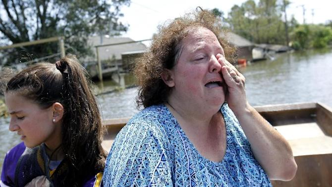 Angela Serpas cries as she sees her flooded home for the first time since Hurricane Isaac pushed a 10-foot storm surge into Braithwaite, La., Saturday, Sept. 1, 2012. At right is her daughter Lainy Serpas, 11.  While New Orleans streets were bustling again and workers were returning to offshore oil rigs, thousands of evacuees couldn't return home to flooded low-lying areas of Louisiana and more than 400,000 sweltering electricity customers in the state remained without power. (AP Photo/Gerald Herbert)