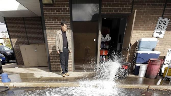 Jong Lee stands by as water is pumped from the flooded basement of his deli in the wake of superstorm Sandy on Thursday, Nov. 1, 2012, in Little Ferry, N.J. Surprise coastal surge floods caused by the storm battered Little Ferry, Moonachie and some other towns along the Hackensack River in Bergen County _ all areas unaccustomed to flooding. (AP Photo/Mike Groll)