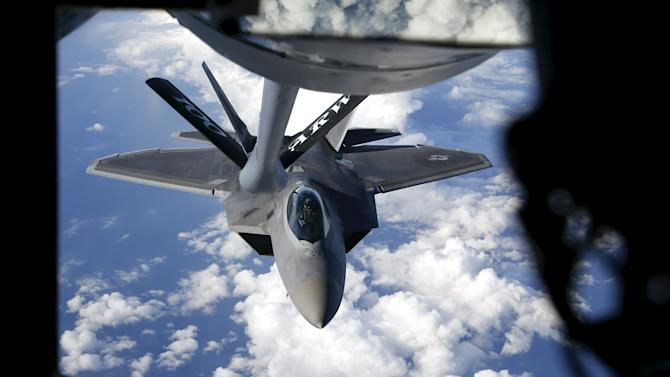 A F-22 Raptor fighter jet is being refuelled by a KC-135 Stratotanker fover the Baltic Sea