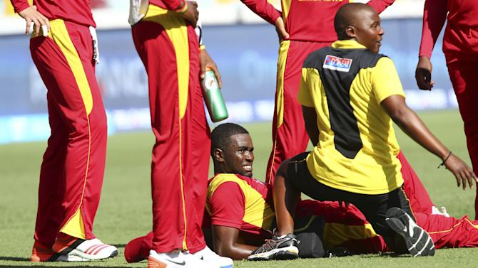 Zimbabwe's Elton Chigumbura, center, is attended to after he got injured during the Pool B Cricket World Cup match against Pakistan in Brisbane, Australia, Sunday, March 1, 2015. (AP Photo/Tertius Pickard)