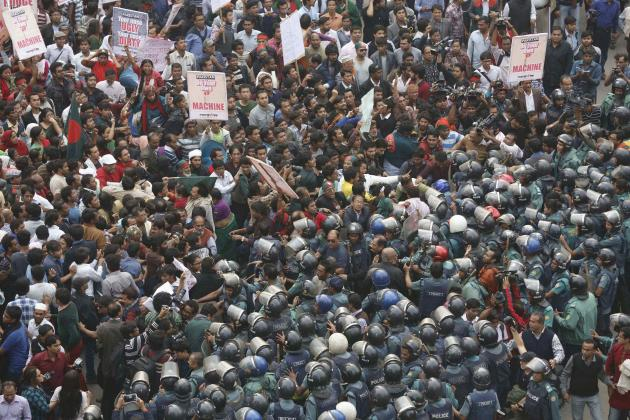 Police try to stop a rally as protesters try to surround and block access to the High Commission of Pakistan in Dhaka