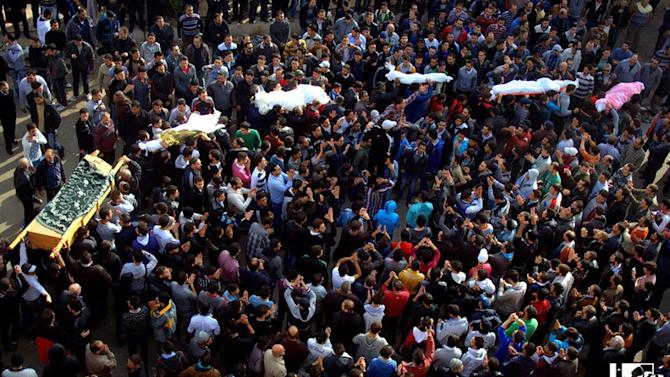 In this citizen journalism image provided by Lens Young Homsi, which has been authenticated based on its contents and other AP reporting, anti-Syrian regime mourners carry the coffins of Syrian civilian who where killed by the shelling of Syrian forces loyal to president Bashar Assad, in Homs, Syria, Monday Dec. 3, 2012. Syrian warplanes on Monday bombed a security building that had been taken over by rebels along the Turkish border, killing at least one person, wounding tens and sending dozens of civilians fleeing across the frontier, a Turkish official said. (AP Photo/Lens Yong Homsi)