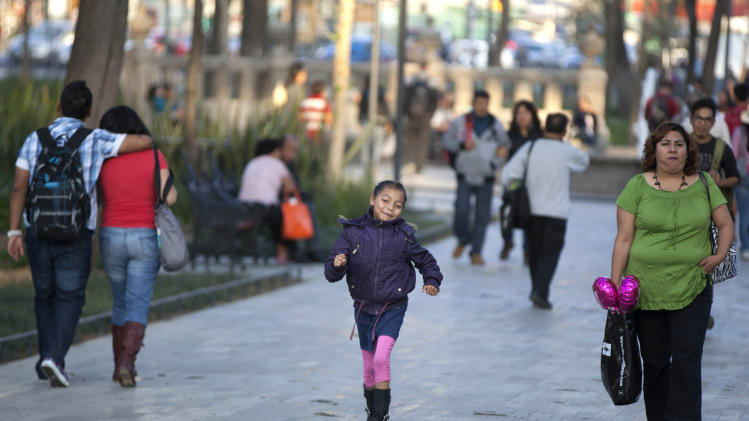"A child skips along a walkway in Alameda Central in Mexico City, Wednesday, Dec. 26, 2012.  Made iconic in the Diego Rivera mural ""Dream of a Sunday Afternoon in the Alameda,"" some of the plaza's concrete sidewalks were replaced by marble, and makeshift vendor stands were kicked out. An ambitious, multimillion-dollar program to beautify public spaces by Mexico City's government is winning praise from urban planners and many residents. (AP Photo/Alexandre Meneghini)"