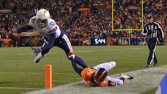 San Diego Chargers wide receiver Keenan Allen (13) stretches the ball across the goal line for a touchdown against Denver Broncos free safety Michael Huff (29) in the fourth quarter of an NFL AFC division playoff football game, Sunday, Jan. 12, 2014, in Denver