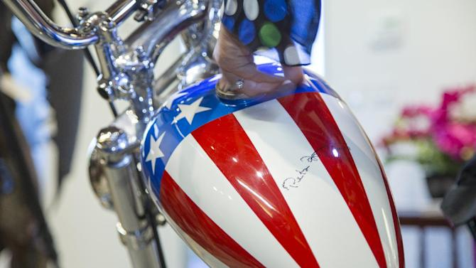 """This Thursday, Sept. 4, 2014 photo shows the autographed gas tank of the Captain America chopper Peter Fonda rode in """"Easy Rider"""" at the Profiles in History auction house in Calabasas, Calif. It's one of the most recognizable motorcycles of all time. The auction house Profiles in History tells The Associated Press it estimates the Harley-Davidson will bring between $1 million and $1.2 million at its Oct. 18, 2014 sale. (AP Photo/Damian Dovarganes)"""