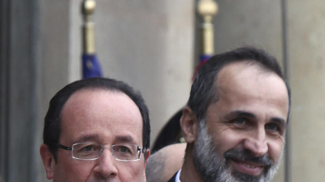 French President Francois Hollande, left, gestures as he welcomes head of the new Syrian National Coalition for Opposition and Revolutionary Forces Mouaz al-Khatib, right, prior to a meeting, at the Elysee Palace, in Paris, Saturday, Nov. 17, 2012. France has taken a leading role among Western countries in supporting Syria's rebels. On Tuesday, it became the first Western nation to formally recognize Syria's newly formed opposition coalition as the sole legitimate representative of the Syrian people. (AP Photo/Thibault Camus)