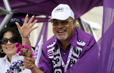 Suriname's President Bouterse smiles at supporters next to his wife Ingrid outside the Central Main Polling Station as he arrives to register for the May 25 general elections, in Paramaribo