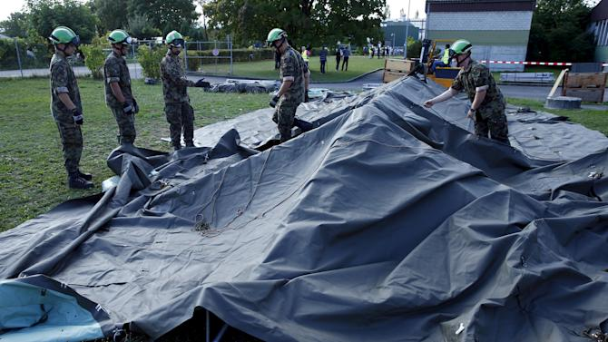 Swiss Army personnel build a tent outside a refugee camp in Lyss
